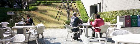 大学構内の広場で、老夫婦が弁当持参で散歩。ここは昔14号館があったところ。