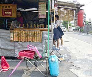小学生の女の子が帰宅途中に焼鳥屋で一杯。熊本ならではの光景。