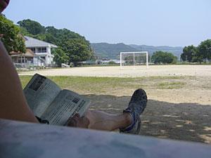 親を待つ間、廃校の運動場で読書。