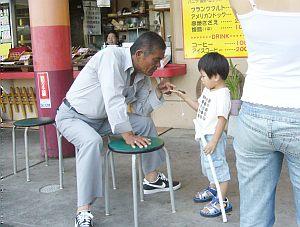 土産物屋のおじさんが、客の子どもと遊ぶの図。セミに糸をくくりつけて玩具にしてた模様。