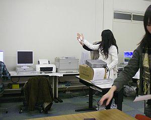 プロジェクタの光を手ですくう学生。Windowsマークを手にかざしてどうする(笑)