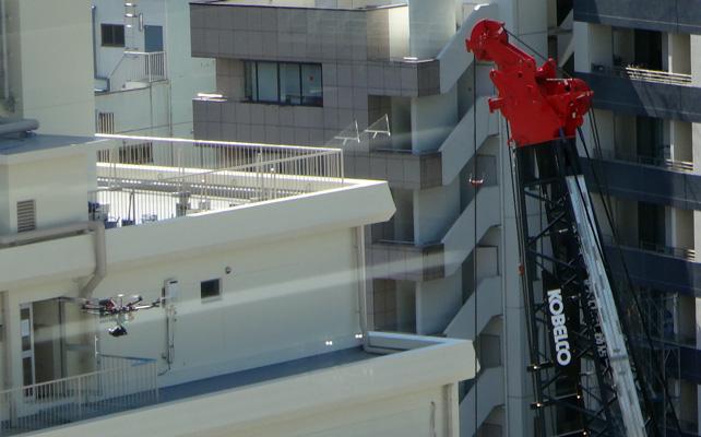 窓の外にドローンが。工事現場を撮影中かな?
