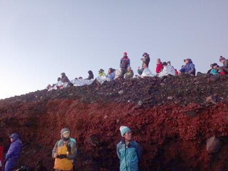 崖の上で日の出を待つ人達